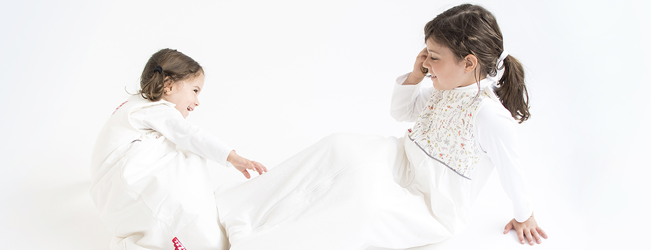 Two girls wearing breathable baby sleeping bags made from organic cotton and Swisswool